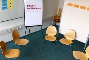 Stuhlkreis mit Flipchart und Pinnwand im Hintergrund